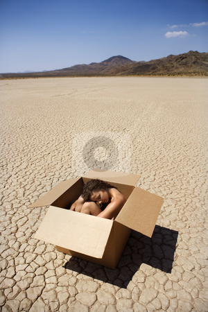 Woman in a box in the desert stock photo, Pretty nude young woman sitting in box in cracked desert landscape in California. by Iofoto Images