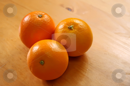 Three oranges stock photo, Three whole raw unpeeled oranges on wooden background by Kheng Guan Toh