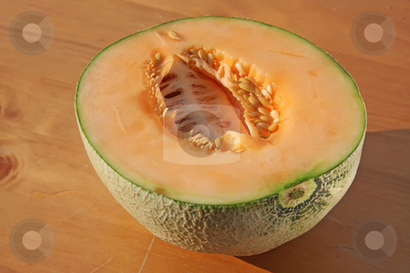 Rockmelon stock photo, Cut half fresh rockmelon on wooden background by Kheng Guan Toh