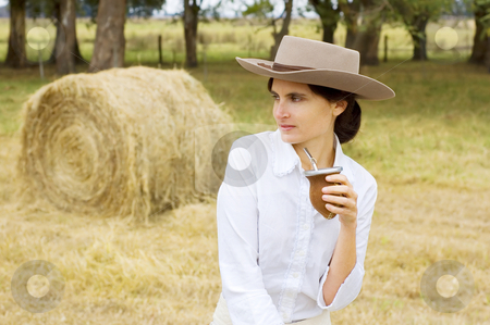 Farm Girl Relaxing stock photo, A typical Argentinean gaucha (cowgirl) drinking yerba mate by Lee Torrens
