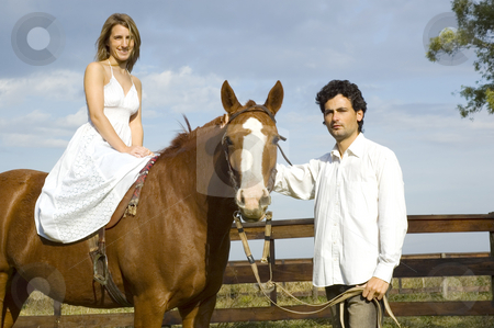 Woman sitting on horse stock photo, A young couple with their horse - the woman riding and the man leading by Lee Torrens