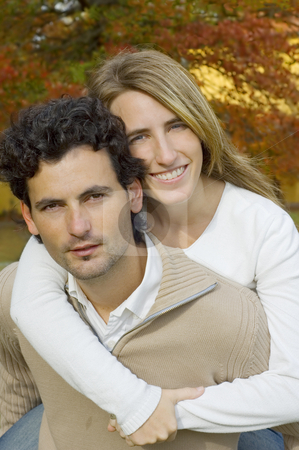 Couple Hugging stock photo, A young couple playing affectionately in a garden during Autumn by Lee Torrens