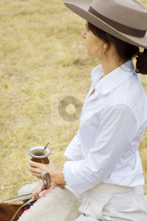 Argentinean Gaucha on her Horse stock photo, A young Argentinean gaucha relaxing with yerba mate while riding her horse. by Lee Torrens