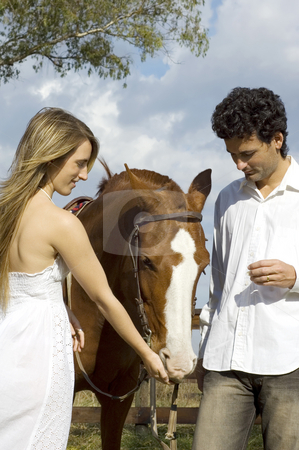 Couple feeding horse stock photo, A young couple relaxing with their horse on a rural farm on a cloudy day by Lee Torrens
