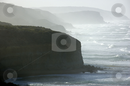 A rugged coastline stock photo, Rough waves batter the cliffs of a rugged coastline. by Lee Torrens