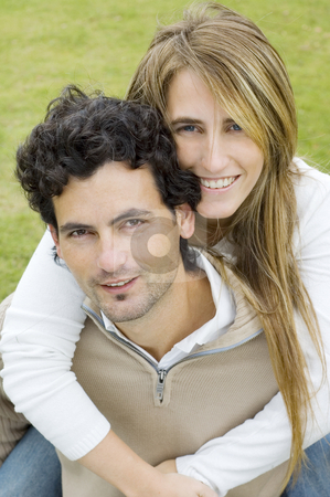 Young couple stock photo, A young couple playing affectionately in a garden, both looking at the camera by Lee Torrens
