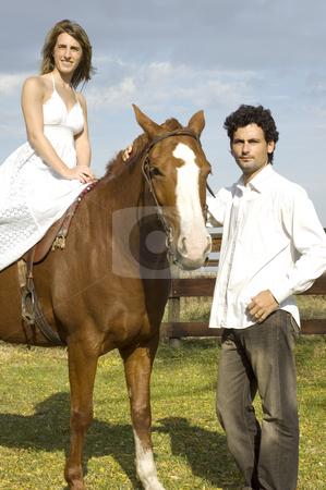 Woman on horseback stock photo, A young couple with their horse - the woman riding and the man leading by Lee Torrens