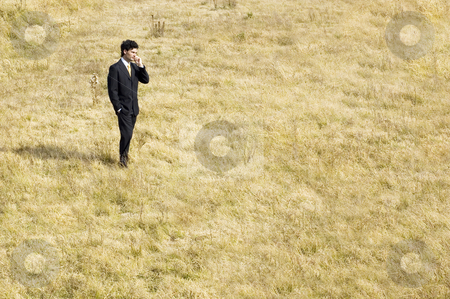 Remote Call stock photo, A young businessman making a phone call in the middle of a dry field. by Lee Torrens