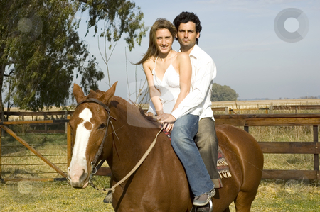 Couple on horseback stock photo, A young couple riding their horse on a rural farm on a cloudy day by Lee Torrens