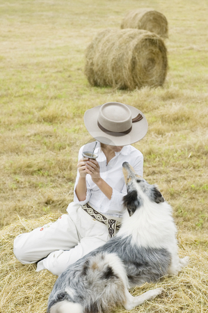 Farm Girl Relaxing with her Dog stock photo, A young Argentinean farm girl and her dog share a moment while relaxing in a field by Lee Torrens