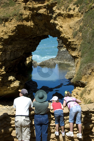 Tourists inspecting The Grotto stock photo, The Grotto is a natural rock formation created by erosion. It is located along the Great Ocean Road in Australia. by Lee Torrens