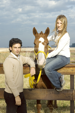 Man holding lead rope stock photo, A young couple posing with their horse by the fence on a rural farm on a cloudy day by Lee Torrens