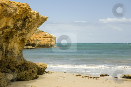 Rocks and a Beach stock photo, A rocky outcrop gives way to a pleasant sandy beach. by Lee Torrens