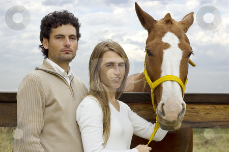 Couple standing by horse stock photo, A young couple posing with their horse at the stable by Lee Torrens