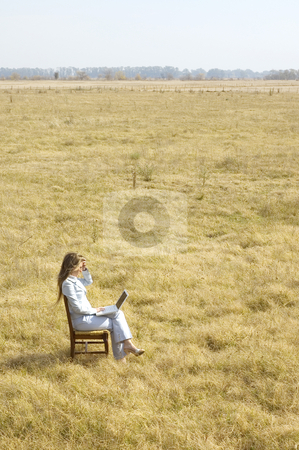 Working Outdoors stock photo, A young business woman working on a laptop in the middle of a dry field. by Lee Torrens