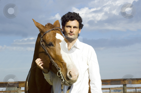 Man and horse stock photo, A young latin man standing with his horse on a cloudy day by Lee Torrens