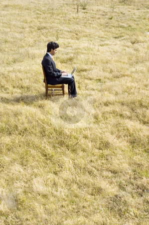 Working Outdoors stock photo, A young business man working on a laptop in the middle of a dry field. by Lee Torrens