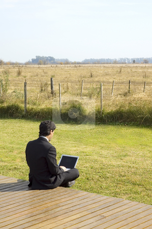 Working Outdoors on the Farm stock photo, A young businessman working on a laptop in a rural property by Lee Torrens