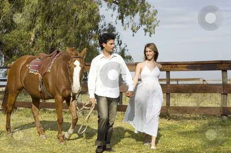 Couple walking horse stock photo, A young couple walking with their horse by Lee Torrens