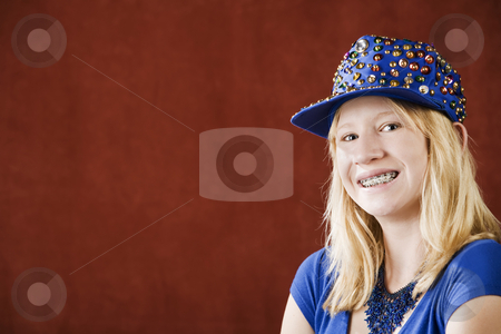 Pretty young girl with braces  stock photo, Teenage girl with braces wearing a hat with sequins by Scott Griessel