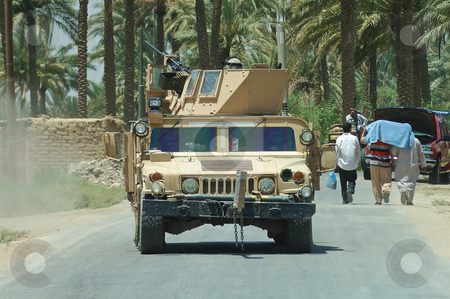 US Humvee in Iraq stock photo, A US humvvee driving towards the camera on an Iraqi road with some civilians walking nearby by Stefan Edwards