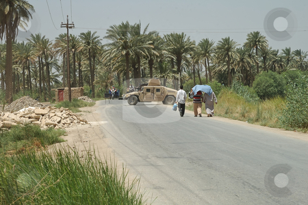 US Military Humvee on Iraqi road stock photo, A US humvee parked across an Iraqi road with several civilians walking towards it by Stefan Edwards