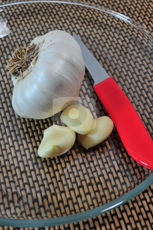 Garlic Cloves And Knife stock photo, Whole garlic and pealed cloves on  clear glass plate with a red handled knife. by Lynn Bendickson