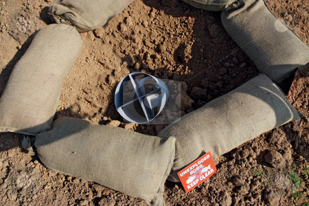 Bomb Crater stock photo, Bomb crater and unexploded bomb with warning signs and sandbags by Paul Phillips