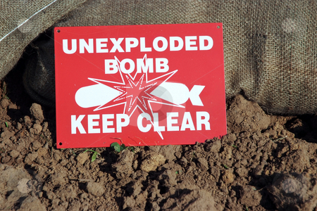 Unexploded stock photo, Unexploded Bomb sign next to sand bags and soil by Paul Phillips
