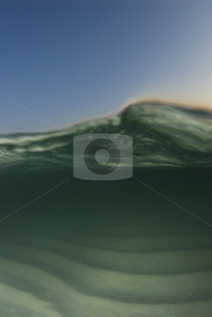 Under Over Curl stock photo, Curl of a passing wave on an underwater/overwater shot image with the blue sky and color from the setting sun rim lighting the wave. by A Cotton Photo