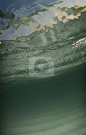 Underwater Beach stock photo, Underwater view of the sea floor with the ocean surface and the bright blue sky and setting sun showing through the surface. by A Cotton Photo