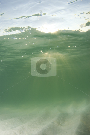 Underwater Beach Sun rays Centered stock photo, A view of the rippled ocean floor, the action on the surface, and the sky and golden sunset rays breaking through the water.  Sunrays centered. by A Cotton Photo