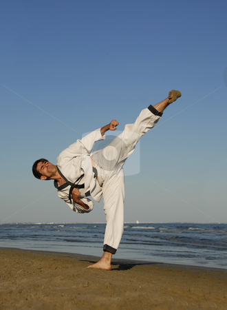 Karate on the beach stock photo, A young man is training in taekwondo on the beach by Bonzami Emmanuelle