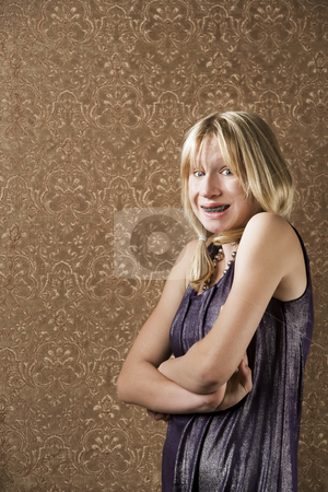Young blonde girl with braces stock photo, Blonde teenager with braces in a party dress by Scott Griessel