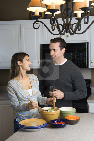 Couple in kitchen. stock photo, Caucasian couple making salad at kitchen counter. by Iofoto Images