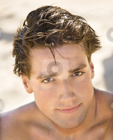 Handsome man. stock photo, Head and shoulder portrait of handsome man on beach. by Iofoto Images