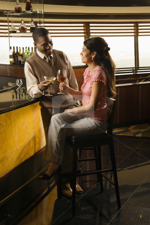 Couple toasting drinks. stock photo, Mid adult African American man toasting Hispanic woman at bar. by Iofoto Images
