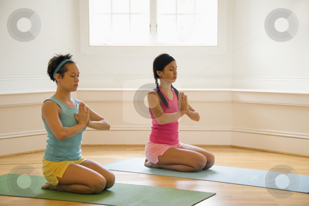 Women doing yoga stock photo, Two young women sitting on yoga mats with eyes closed holding hands in prayer position. by Iofoto Images