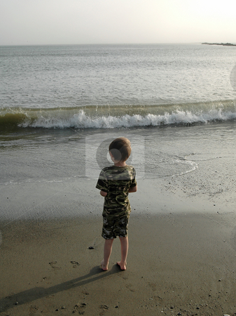 Boy at Beach stock photo, As the day comes to an end, this young boy watches the waves roll in on the pacific ocean. The beach is near Ocean Shores, Wa. by Tim Thompson