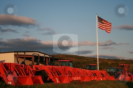 Kubotas under the US Flag stock photo, Kubota equipment under a blue sky and the US flag by Tom and Beth Pulsipher