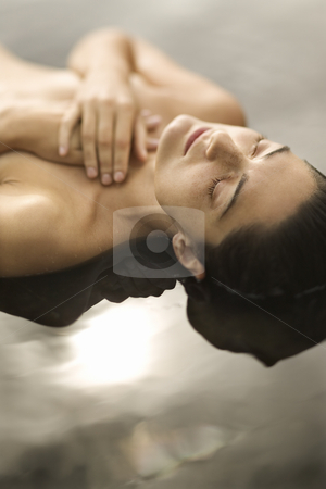 Woman in water. stock photo, Close up of young nude Caucasian woman lying on back in water with eyes closed and hands crossed on chest. by Iofoto Images