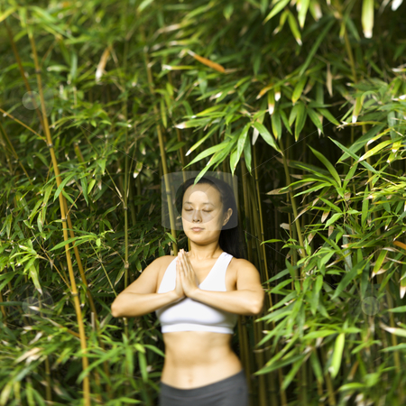 Asian woman meditating. stock photo, Half length portrait of Asian American woman in fitness attire standing in yoga position in bamboo forest in Maui, Hawaii. by Iofoto Images