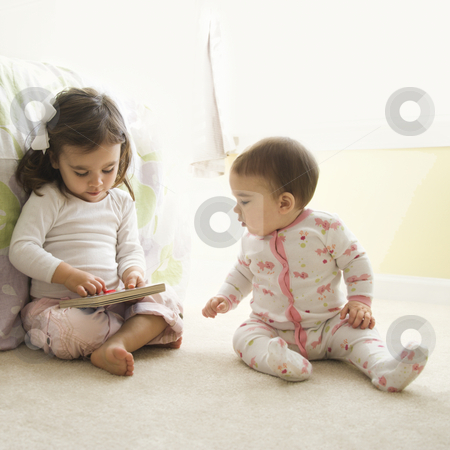 Girls with book. stock photo, Caucasian girl children sitting on bedroom floor looking at book. by Iofoto Images