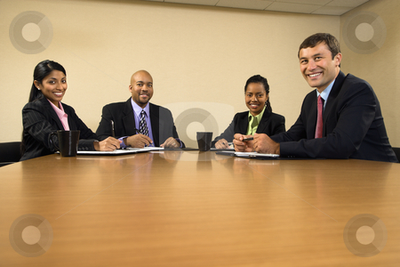 Happy business meeting. stock photo, Businesspeople sitting at conference table smiling. by Iofoto Images