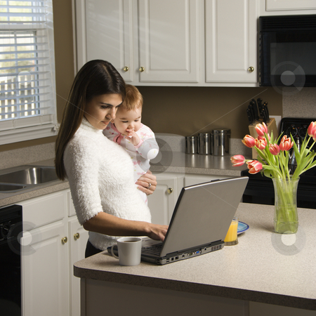 Mother with baby. stock photo, Caucasian woman holding baby  and typing on laptop computer in kitchen. by Iofoto Images