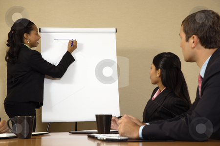 Leadership businesswoman. stock photo, Businesspeople sitting at conference table  while businesswoman gives presentation. by Iofoto Images