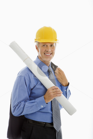Construction site supervisor. stock photo, Caucasian middle aged businessman holding blueprints and wearing hard hat. by Iofoto Images