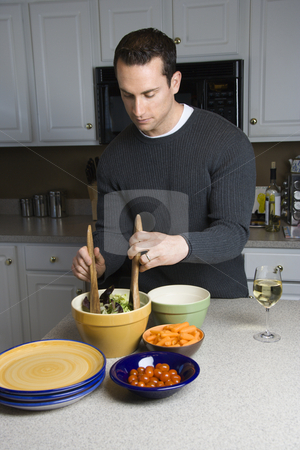 Man making salad. stock photo, Caucasian man making salad on kitchen counter. by Iofoto Images