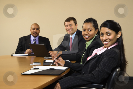 Smiling businesspeople. stock photo, Businesspeople sitting at conference table smiling. by Iofoto Images