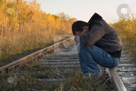 Severe Depression stock photo, A man suffering from severe depression, sitting on some train tracks by Richard Nelson